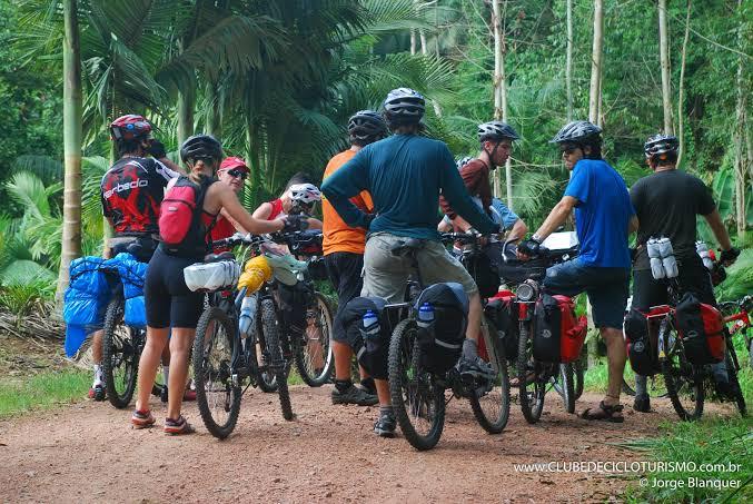 Na imagem, um grupo de ciclistas se reúnem em uma trilha em meio a natureza.