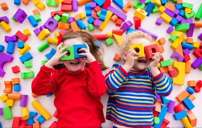 Duas crianças felizes brincam com blocos coloridos de construir brinquedos.