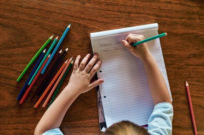 A imagem é tirada de cima, dá para ver as mãos de uma criança escrevendo sobre o papel. Que, por sua vez, está sobre a mesa, onde estão os outros lápis em cima.