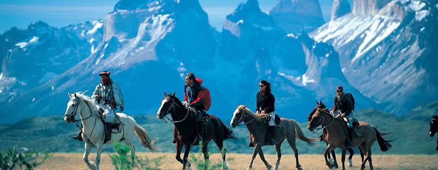 Na imagem, quatro homens montado em cavalos e se posicionam em fila indiana, um atrás do outro.