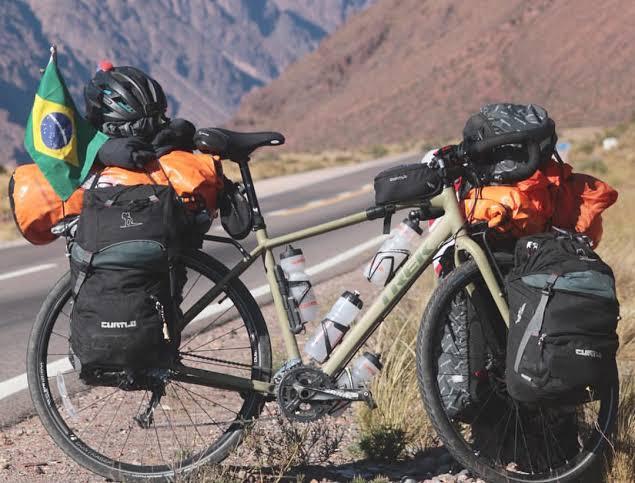 Na imagem, uma bicicleta com uma pequena bandeira do Brasil pendurada, é fotografada junto de algumas mochilas por perto.