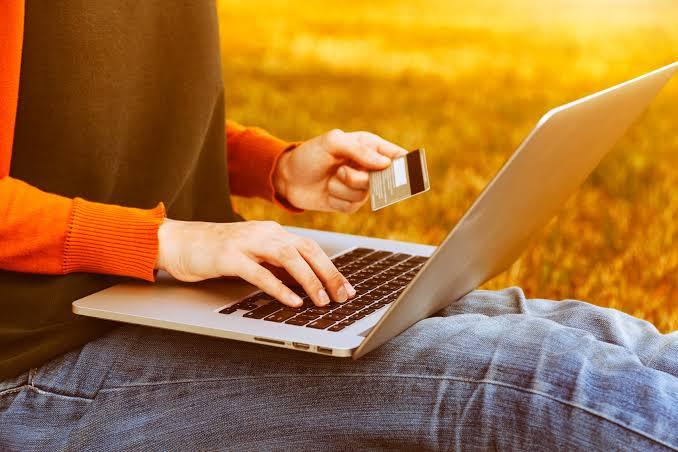 Na imagem, um homem segura seu cartão de crédito e um notebook, simbolizando a compra online que está fazendo.