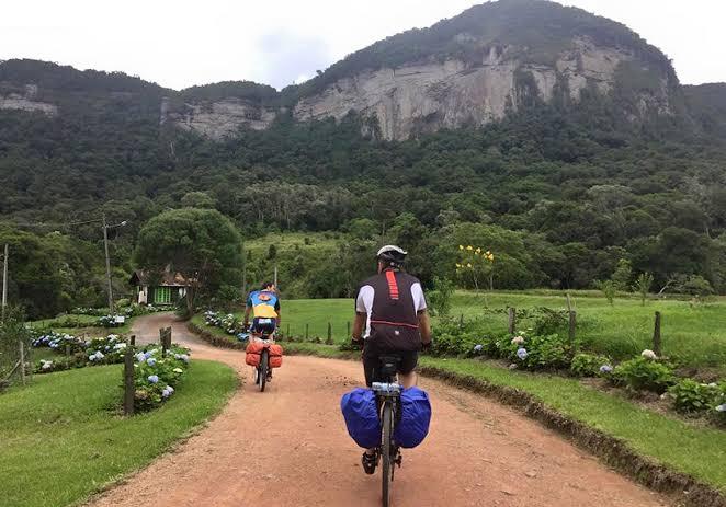 Na imagem, dois ciclistas andam por uma estrada de terra em meio a natureza.