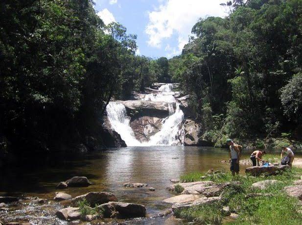 Na imagem há uma pequena cachoeira que forma uma piscina natural com pedras.