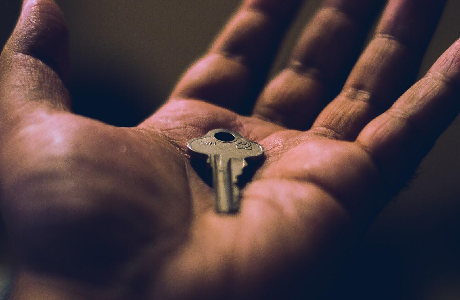 Na imagem, alguém segura uma chave na palma da mão.