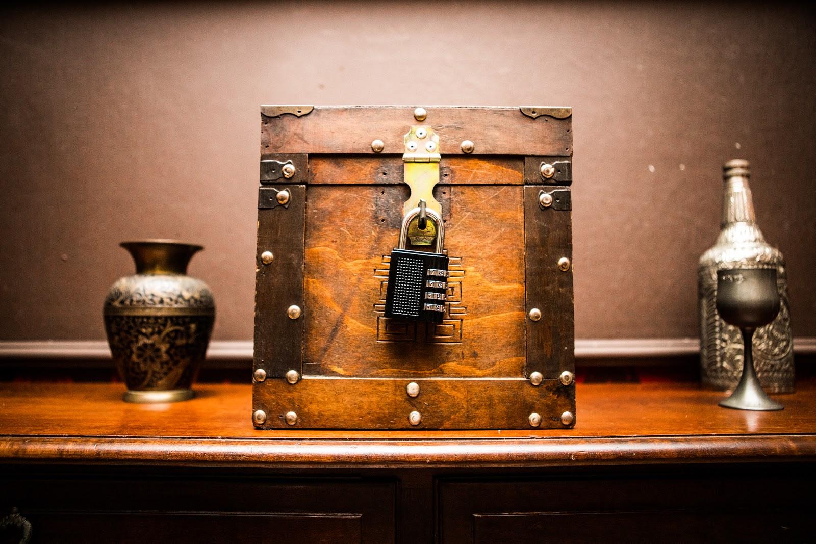 Na imagem, há um baú com um cadeado codificado ao centro. Do lado, dois vasos decorativos.