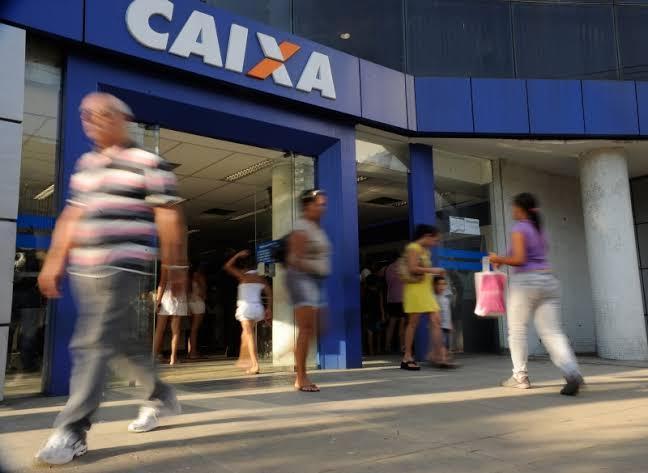 """Na imagem, há um estabelecimento com uma porta grande com o leiteiro """"CAIXA"""" nome do banco a qual ela pertence. Enquanto isso, várias pessoas andam em frente a ela."""