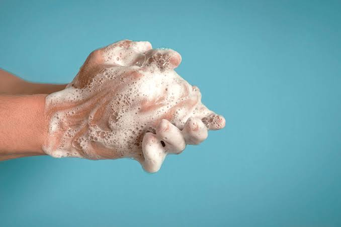 Na imagem, as mãos cheias de espuma estão se esfregando para ficarem limpas.