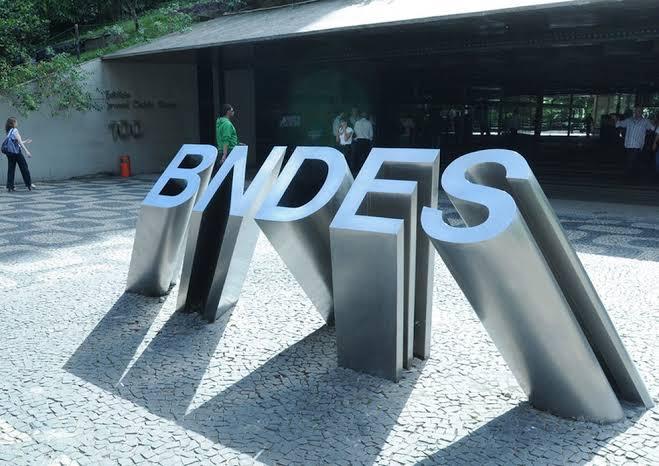 Na imagem, há o letreiro BNDES em uma calçada.