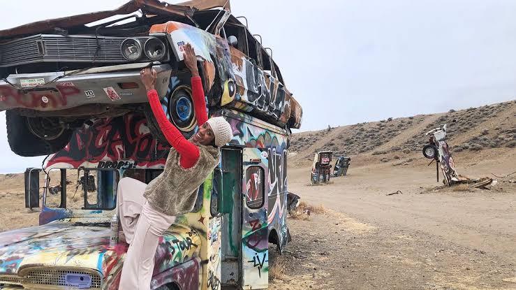 Na imagem há um deserto e carros grafitados e depredados. Em foco, uma moça posa para a foto em um desses carros.
