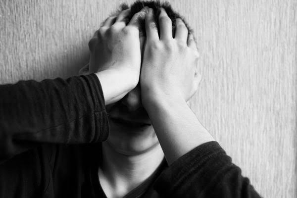 Na imagem, um homem coloca a mão no rosto como quem está em desespero.