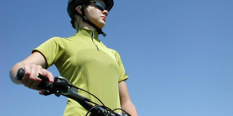 Na imagem, uma mulher segura o guiador da bicicleta, enquanto olha para o horizonte.
